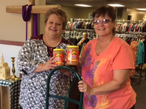 Bank employee and community charity member standing in a thrift store with peanut butter donations.
