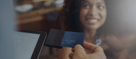 photo of young woman smiling as her credit card purchase is being processed
