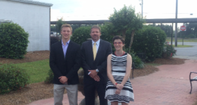 photo of scholarship recipients and bank manager standing outside of school