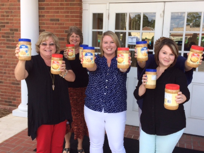 group of ladies enthusiastically holding out jars of peanut butter