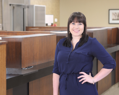 Picture of employee, Carlie Tawzer, wearing a navy dress and standing in the Omega Branch Lobby.