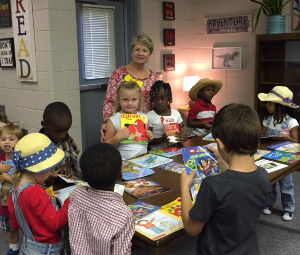 Cordele employee with elementary school students and their books.