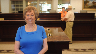 photo of older female standing in bank lobby smiling for camera