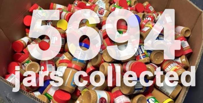 Collection bin of peanut butter with 5,694 jars collected written across the photo.