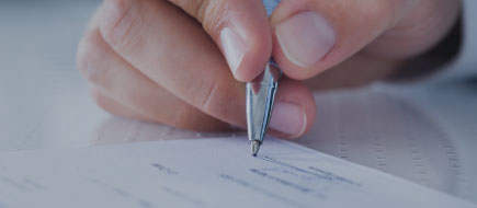 up close photo of a hand holding a pen and signing a check