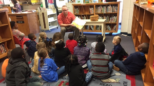 bank employee reading to a group of students in local library