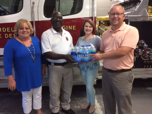 City Fire department and Cordele branch employees standing in front of fire truck, accepting donation of water.