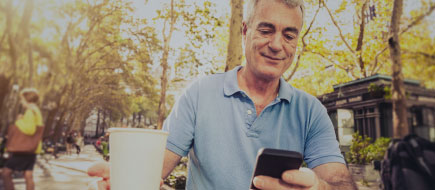 photo of an older man drinking coffee while sitting in a park and working on his mobile phone.