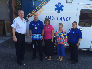 County EMS employees and Cordele Branch employees standing in front of an ambulance, accepting donation of water.