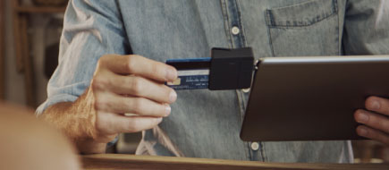 photo of older hands using an ipod and attachment to process a credit card transaction