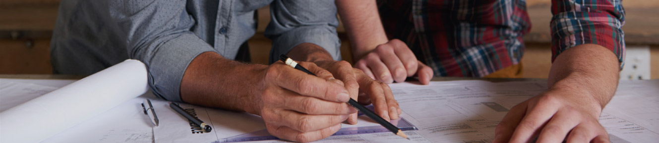 photo of two men drawing out work plans with a pencil