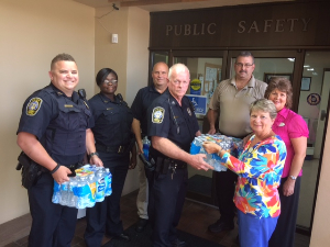 City police officials and Cordele branch employees standing in front of Public Safety sign, accepting donation of water.