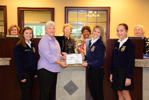 Vienna branch employees and FFA members standing in the bank lobby accepting donation check.