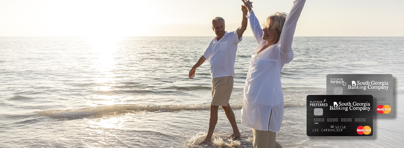 photo of senior couple holding hands and walking through the ocean surf