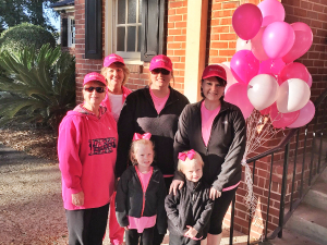 Cordele employees wearing pink hats and holding pink balloons in honor of breast cancer awareness month.