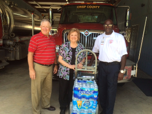 County fire department employee and Cordele branch employees standing in front of fire truck, accepting donation of water.